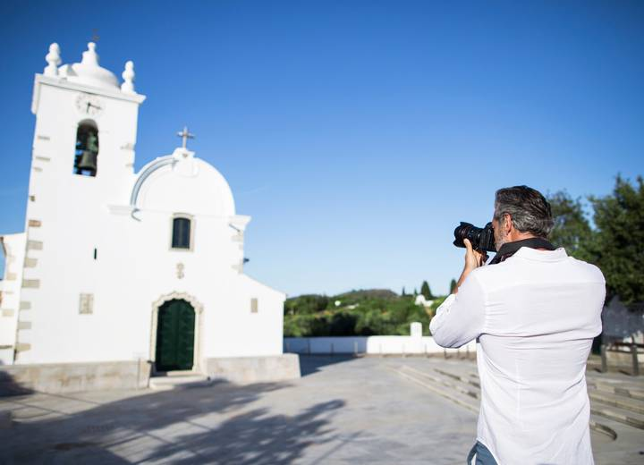 Man taking a photo of Querença's church
