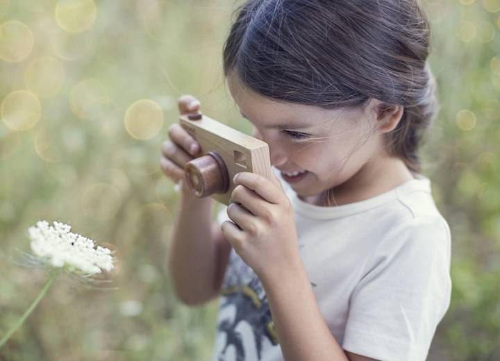 Little girl with a toy camera photographing a flower