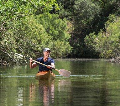 Homem a andar de kayak no rio
