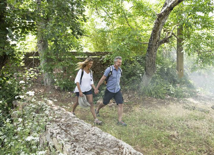 Man and woman walking in the forest that surrounds Ombria Resort