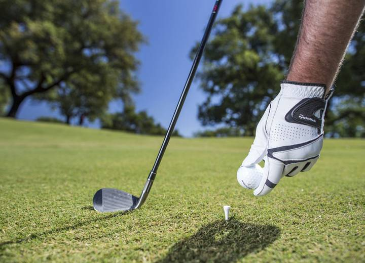 A man's left arm with a white glove, putting a golf ball on a tee, and a golf club, in Ombria's golf course
